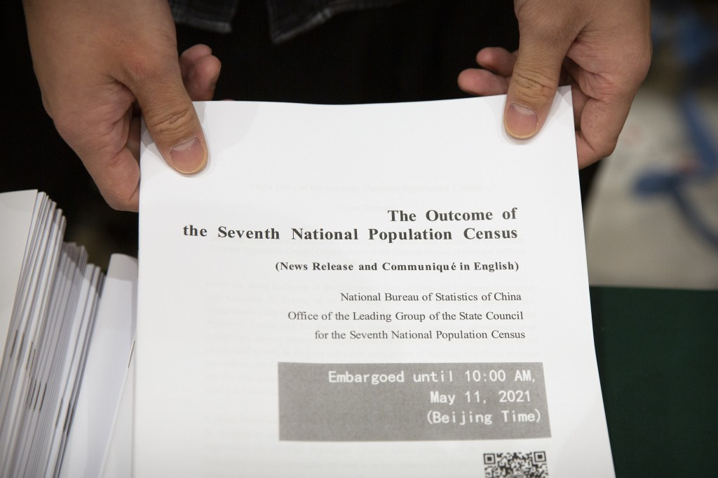 A staff member waits to hand out a copy of a news release outlining the results of China's latest population census before a press conference at the S...