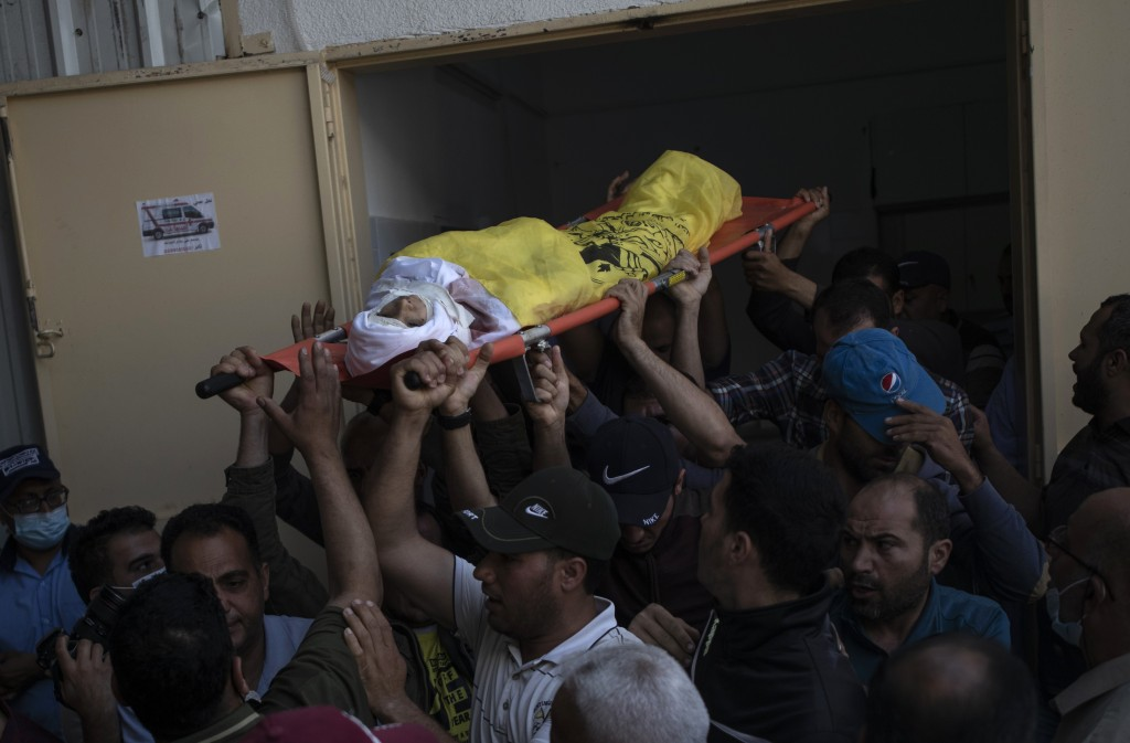 Palestinian mourners carry the body of 11-year-old Hussain Hamad, who was killed by an explosion during the ongoing conflict between Israel and Hamas,...