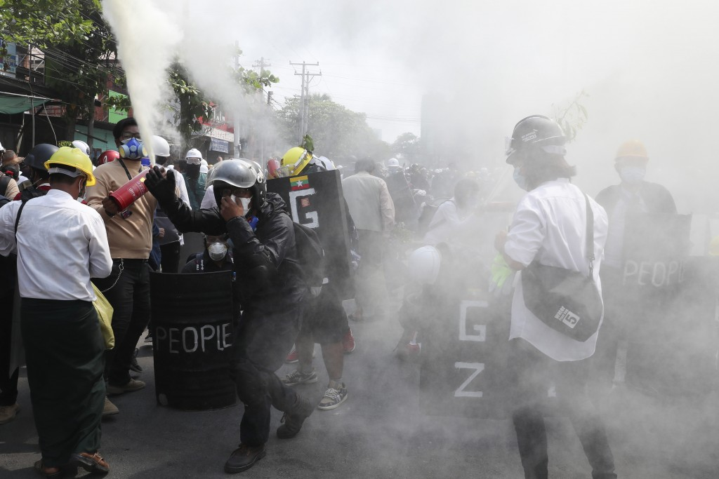 FILE - In this March 7, 2021, file photo, anti-coup protesters discharge fire extinguishers to counter the impact of the tear gas fired by police duri...