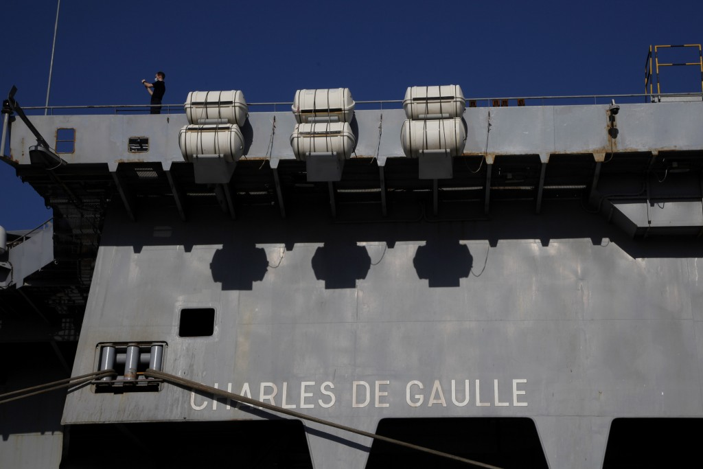 A French crew member stands at France's nuclear-powered aircraft carrier Charles de Gaulle at Limassol port, Cyprus, Monday May 10, 2021.  With the Ta...