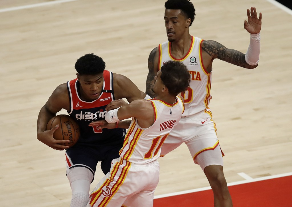 Washington Wizards' Rui Hachimura, left, drives the ball against Atlanta Hawks' Trae Young (11) in the first half of an NBA basketball game Monday, Ma...