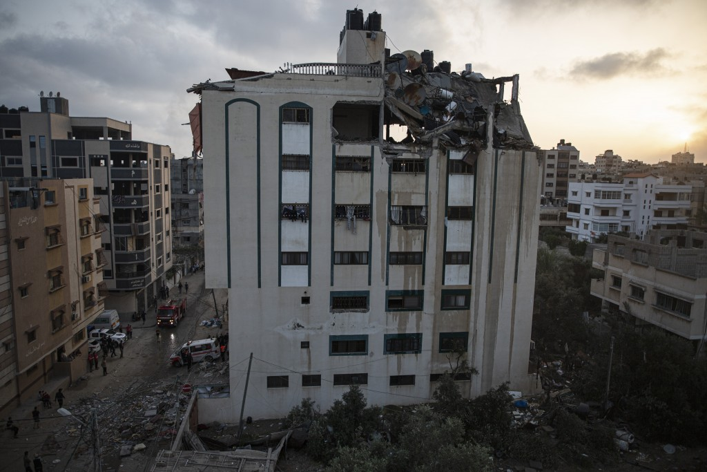 Palestinians search for survivors under the rubble of a destroyed rooftop of a residential building which was hit by Israeli missile strikes, at the S...