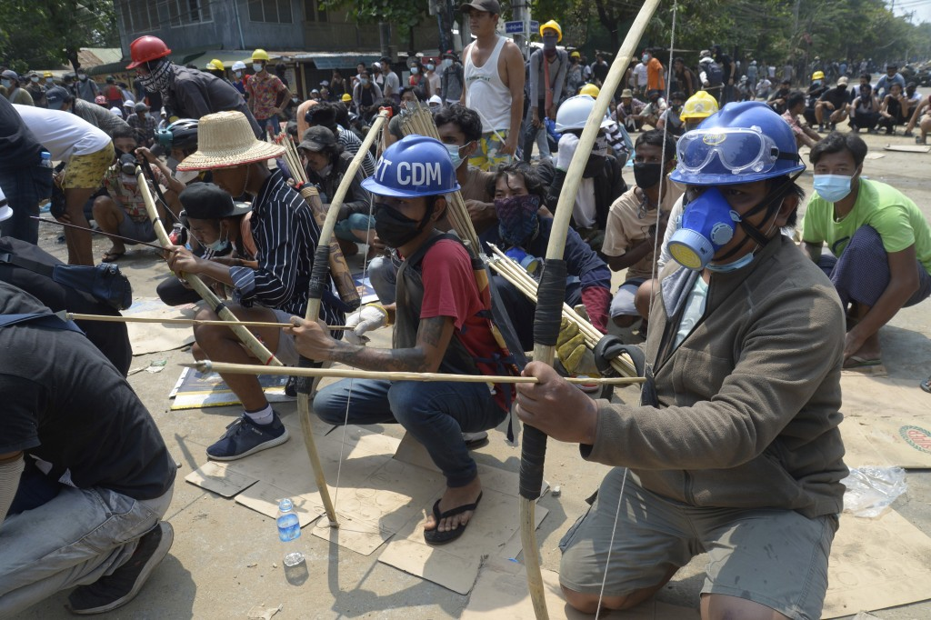 FILE - In this March 27, 2021, file photo, anti-coup protesters prepare makeshift bow and arrows to confront police in Thaketa township Yangon, Myanma...