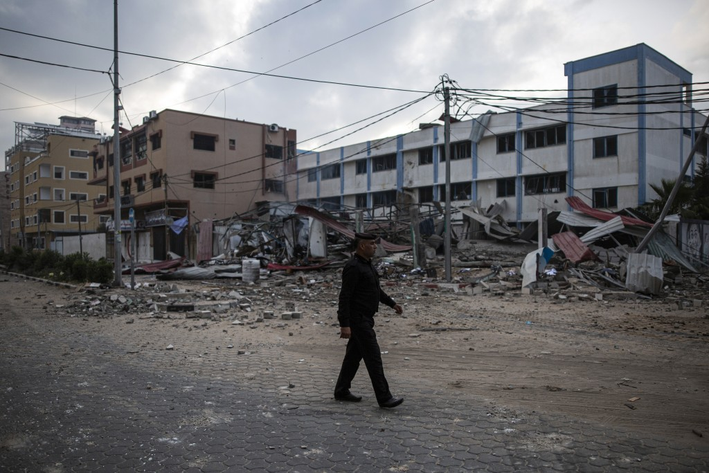 A Palestinian police officer crosses a street next to the remains of a Hamas security building which was hit by Israeli missile strikes, in Gaza City,...