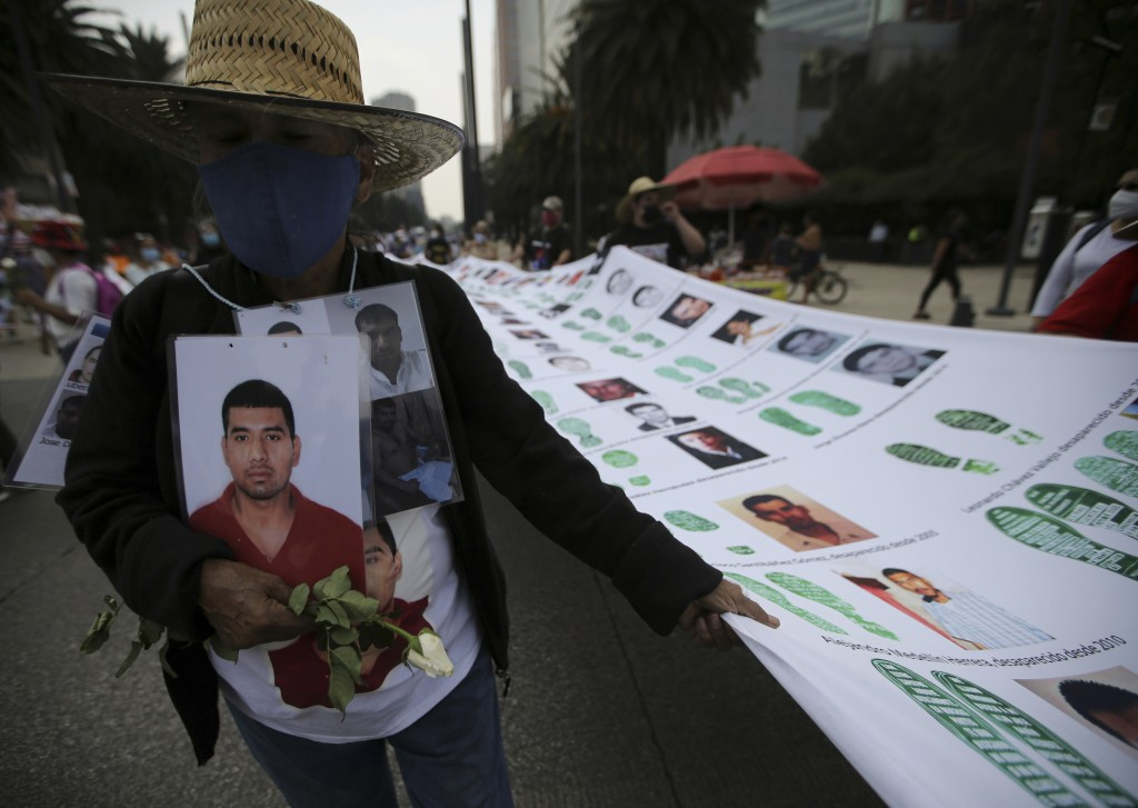 A person holds a portrait during a march in remembrance of those who have disappeared, on Mother's Day in Mexico City, Monday, May 10, 2021. (AP Photo...