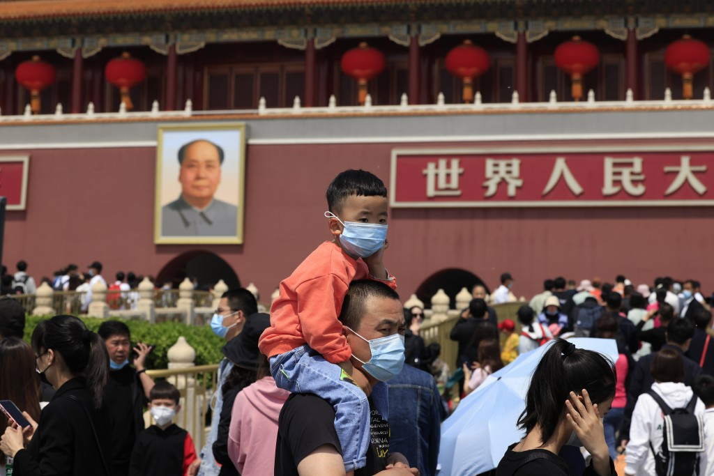 A man and child wearing masks visit Tiananmen Gate near the portrait of Mao Zedong in Beijing on May 3, 2021. China's population growth is falling clo...