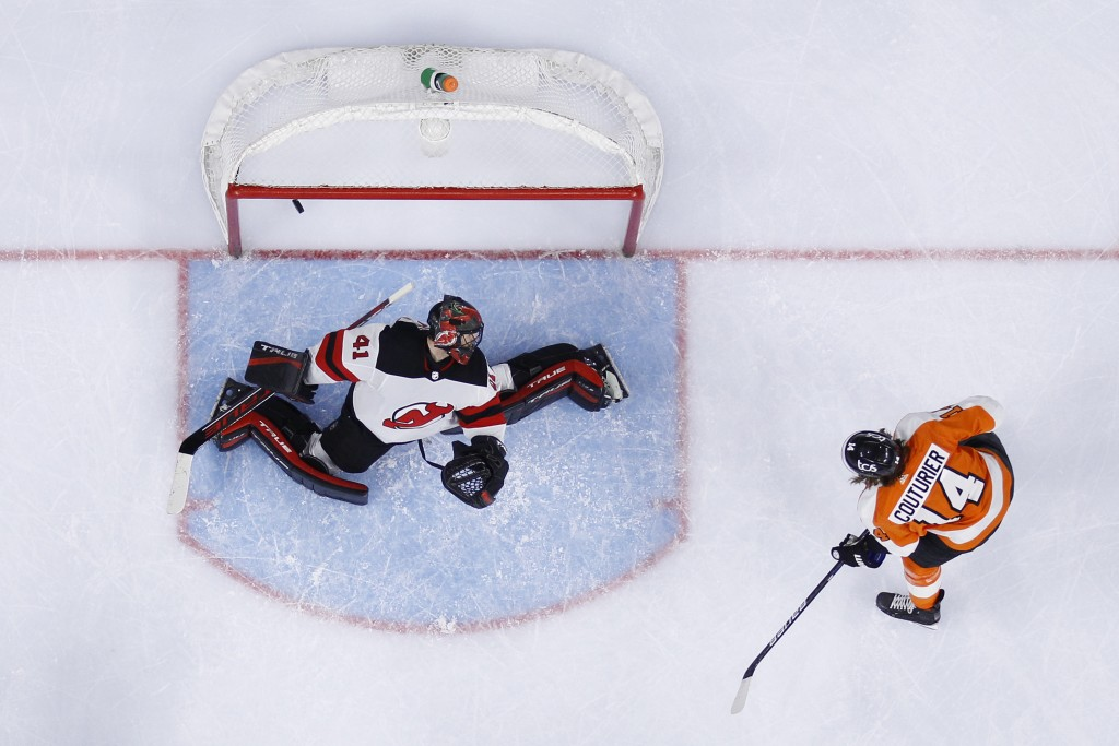 Philadelphia Flyers' Sean Couturier (14) gets a shot past New Jersey Devils' Scott Wedgewood (41) during the second period of an NHL hockey game, Mond...
