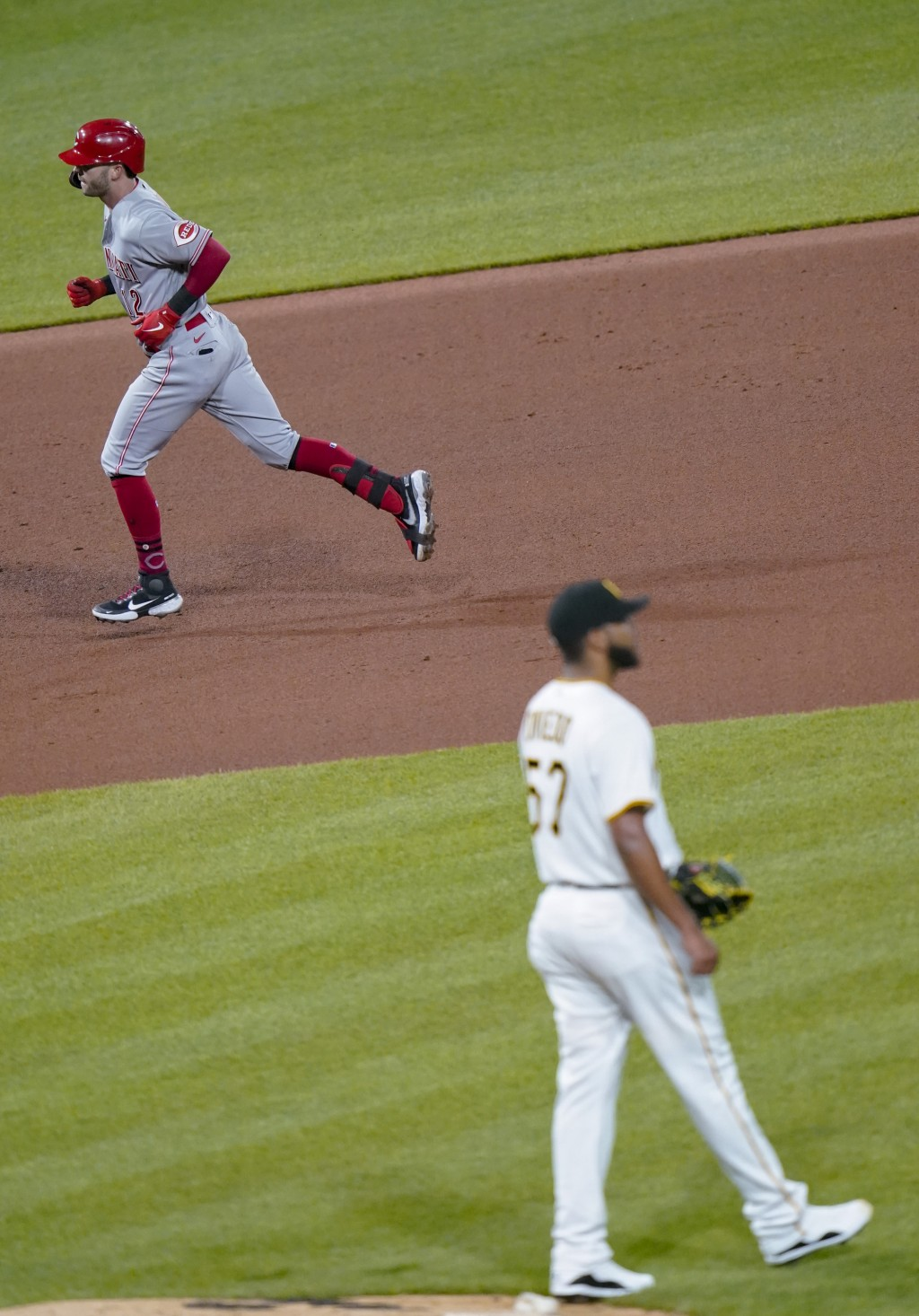 Cincinnati Reds' Tyler Naquin, left, rounds the bases after hitting a three-run home run off Pittsburgh Pirates starting pitcher Luis Oviedo, right, i...