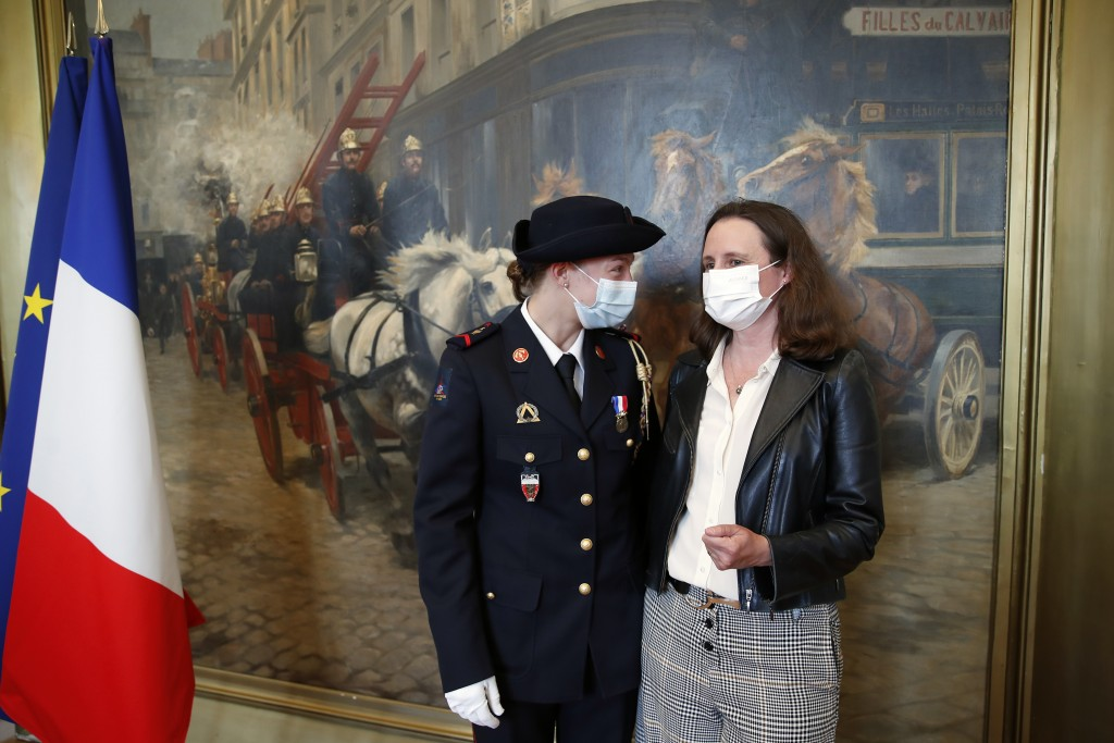 French math teacher-volunteer fighter, Marion Dehecq, left, talks with Paris-based Associated Press journalist Lori Hinnant, after she receives a bron...