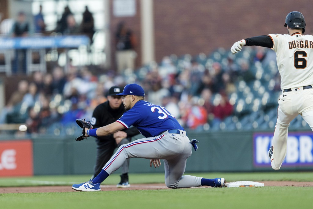 Texas Rangers first baseman Nate Lowe (30) makes the catch for an out against San Francisco Giants' Steven Duggar (6) during the third inning of a bas...