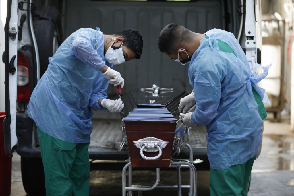 Healthcare workers seal a coffin of a COVID-19 victim patient at Llavallol Dr. Norberto Raúl Piacentini Hospital in Lomas de Zamora, Argentina, Friday...
