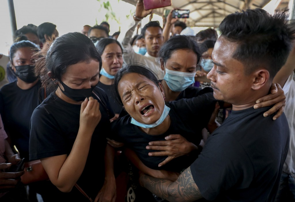FILE - In this Feb. 23, 2021, file photo, Thida Hnin cries during the funeral of her husband Thet Naing Win at Kyarnikan cemetery in Mandalay, Myanmar...
