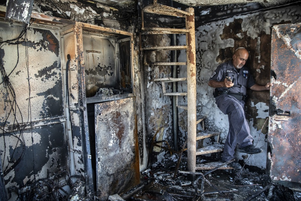 Avi Korkas, a municipality worker, examines the damages of a municipality office in charge of an outdoor food market, that was torched after a night o...