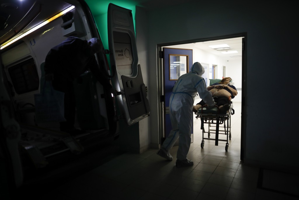 A healthcare worker pushes a woman who is suspected of having COVID-19 into Llavallol Dr. Norberto Raúl Piacentini Hospital in Lomas de Zamora, Argent...