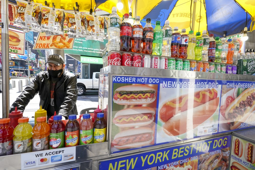 Mohammed Hussein works at his hot dog vending cart in New York's Times Square, Tuesday, April 27, 2021. In recent weeks, tourism indicators for New Yo...