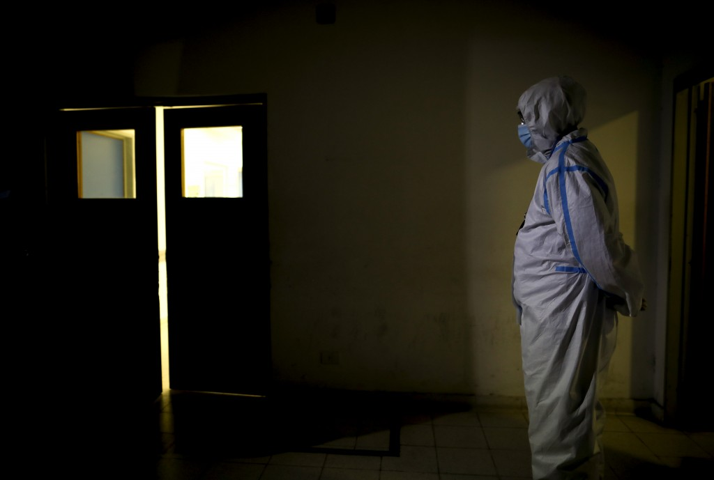 A healthcare worker stands outside Llavallol Dr. Norberto Raúl Piacentini Hospital in Lomas de Zamora, Argentina, Saturday, May 1, 2021, amid the new ...