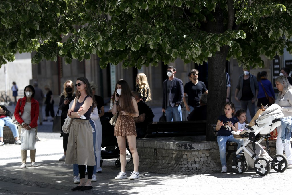 People wait in line in front of a shop in Prague, Czech Republic, Monday, May 10, 2021. The Czech Republic is massively relaxing its coronavirus restr...