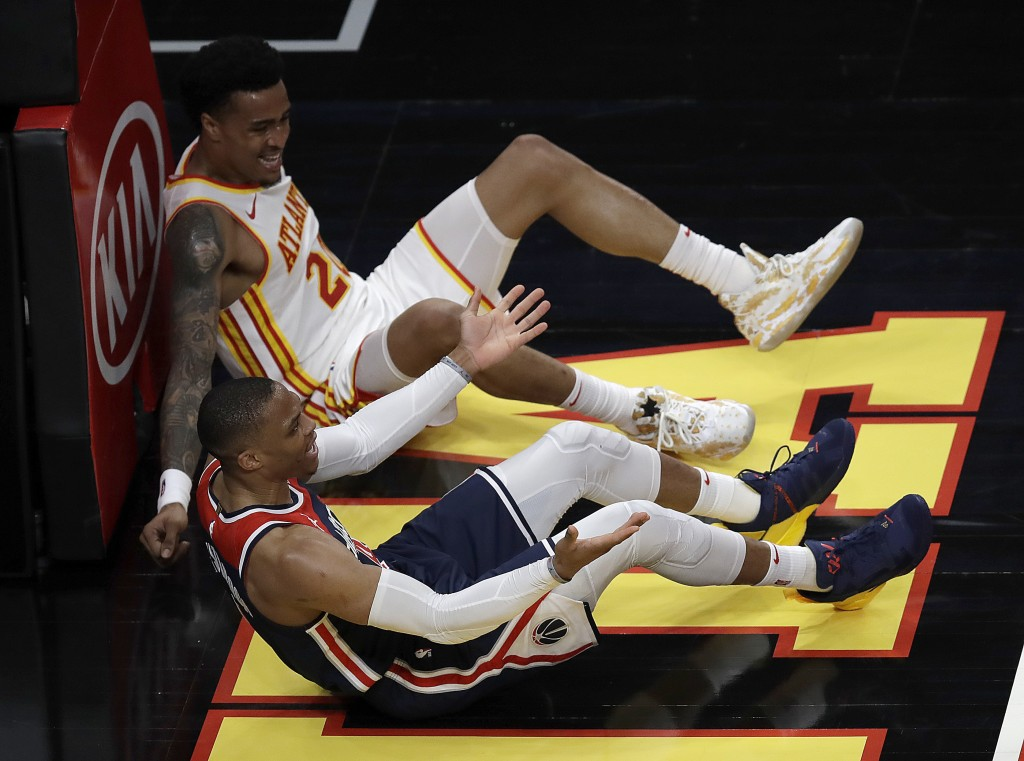 Washington Wizards' Russell Westbrook, foreground, reacts beside Atlanta Hawks' John Collins on the floor in the second half of an NBA basketball game...