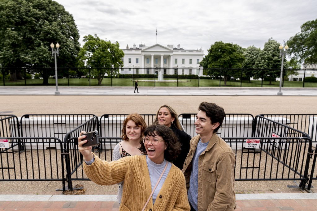 From left, Eliana Lord, Carly Mihovich, Stephanie Justice, and Nick Hansen, visiting from Columbia, S.C., take a photo at Lafayette Park, across the s...