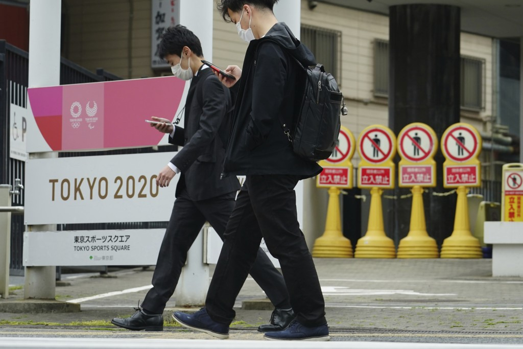 Men wearing protective masks to help curb the spread of the coronavirus walks past a banner for the Tokyo 2020 Olympic and Paralympic Games in Tokyo T...