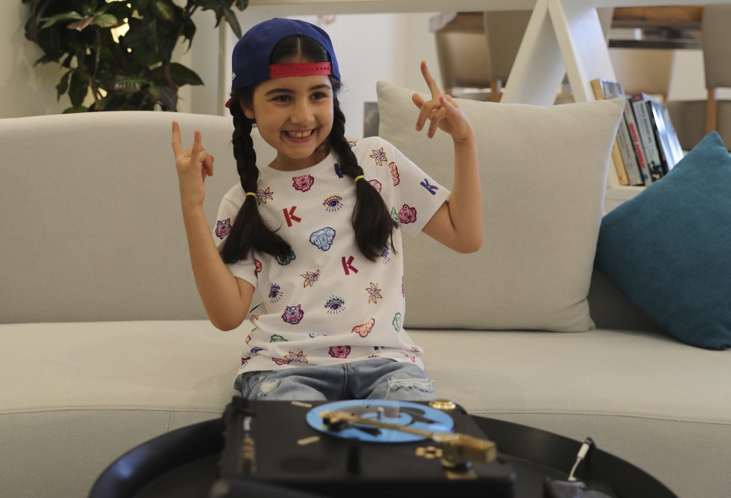Michelle Rasul flashes a rockstar sign in the lobby of her apartment building in Dubai, United Arab Emirates, Sunday, May 9, 2021. Rasul, a 9-year-old...