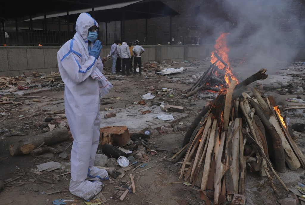 A man wearing personal protective equipment prays in front of the burning funeral pyre of his father who died of COVID-19, at a crematorium in New Del...