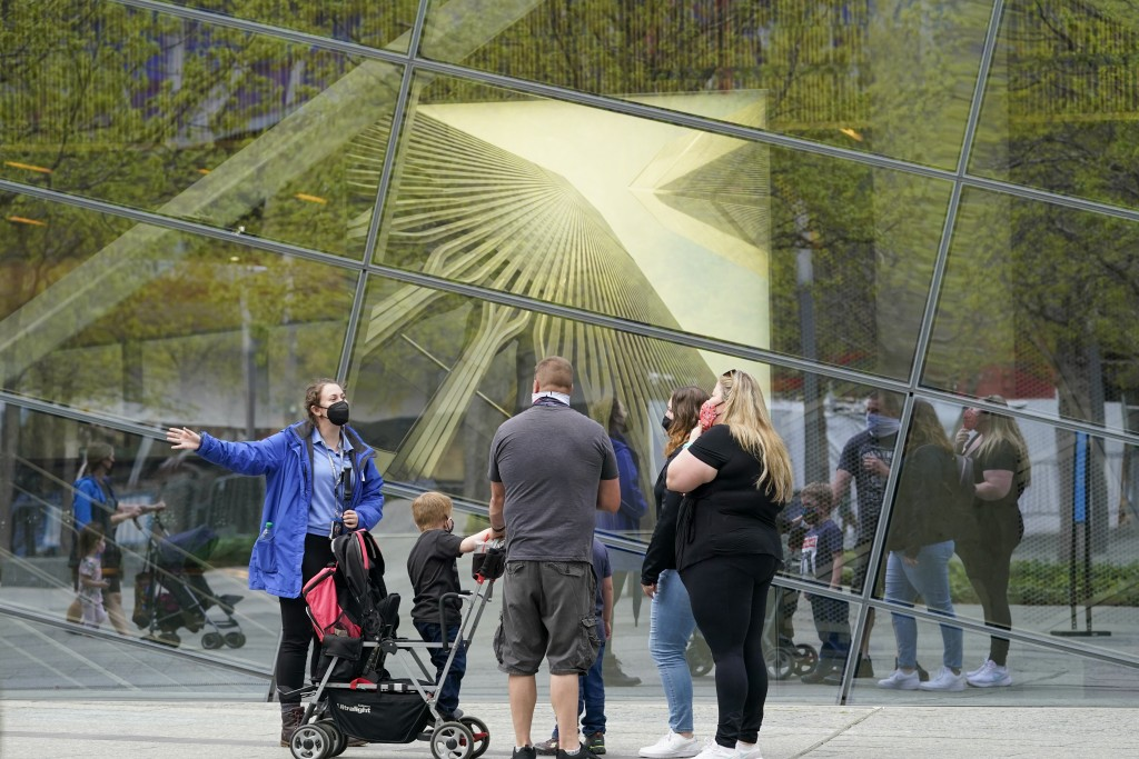 A 9/11 Memorial & Museum Visitor Services associate, left, gives visitors information and directions, Thursday, April 29, 2021, in New York. In recent...