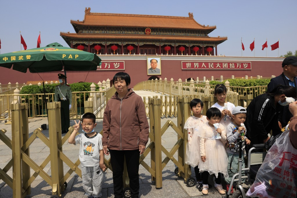 A child makes a gesture and winks as he poses for photos in front of Tiananmen Gate in Beijing on May 3, 2021. China's population growth is falling cl...