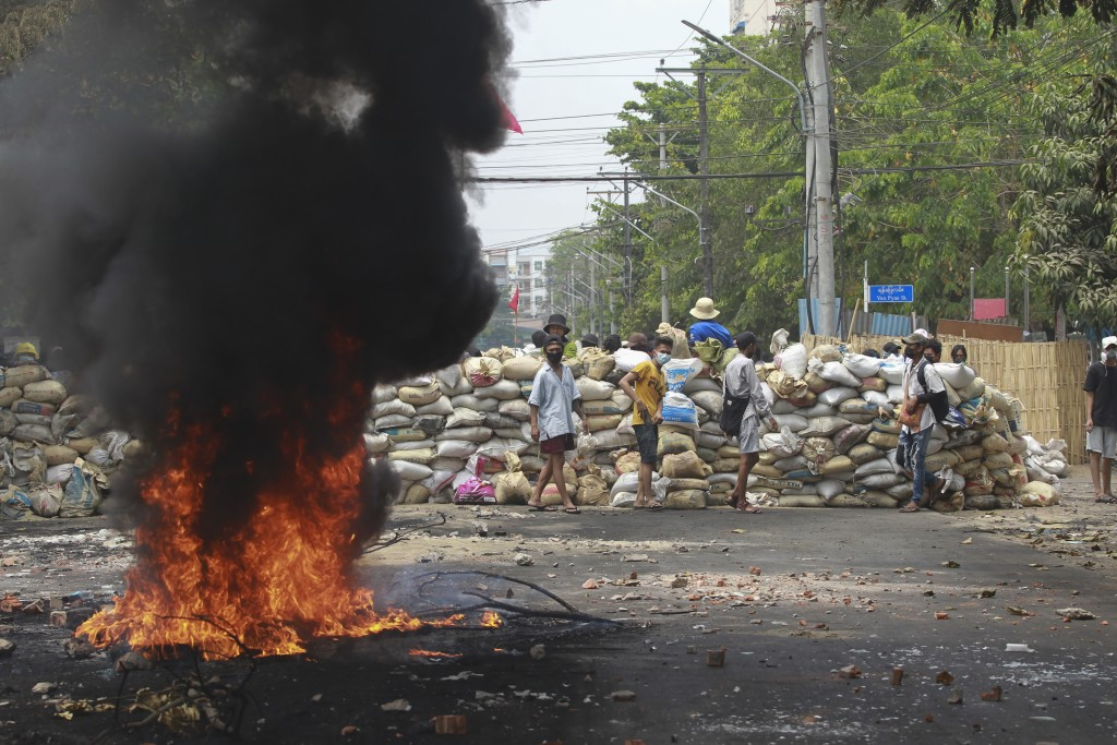 FILE - In this March 30, 2021, file photo, anti-coup protesters stand beside burning tires as they fortify their position against the military during ...