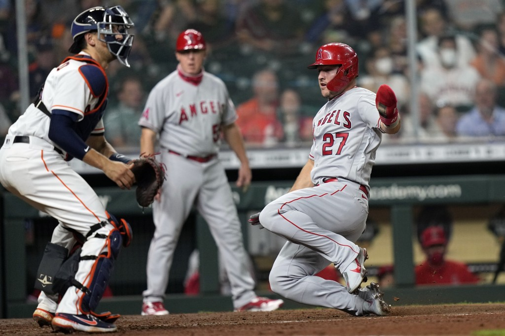 Los Angeles Angels' Mike Trout (27) scores as Houston Astros catcher Jason Castro waits for the throw during the fourth inning of a baseball game Mond...