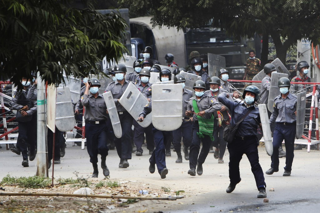 FILE - In this Feb. 20, 2021, file photo, police charge forward to disperse protesters in Mandalay, Myanmar. The military takeover of Myanmar early in...