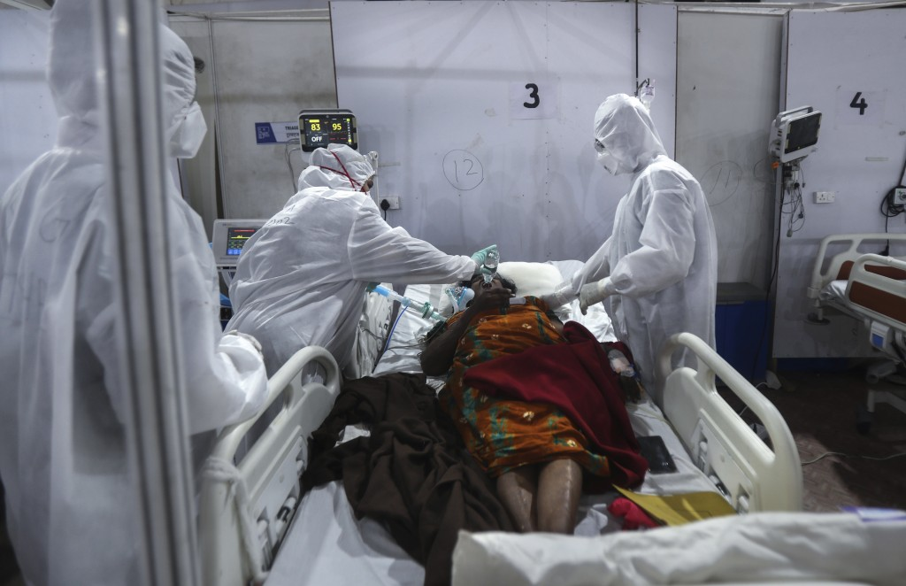 Health workers give water to a patient at the BKC jumbo field hospital, one of the largest COVID-19 facilities in Mumbai, India, Thursday, May 6, 2021...