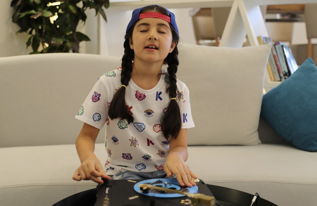Michelle Rasul enjoys scratching her turntable in the lobby of her apartment building in Dubai, United Arab Emirates, Sunday, May 9, 2021. Rasul, a 9-...