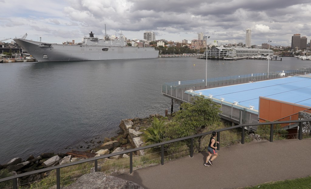 A woman jogs on a track across from where HMAS Canberra is docked at Garden Island naval base in Sydney, Tuesday, May 11, 2021, as the government prep...