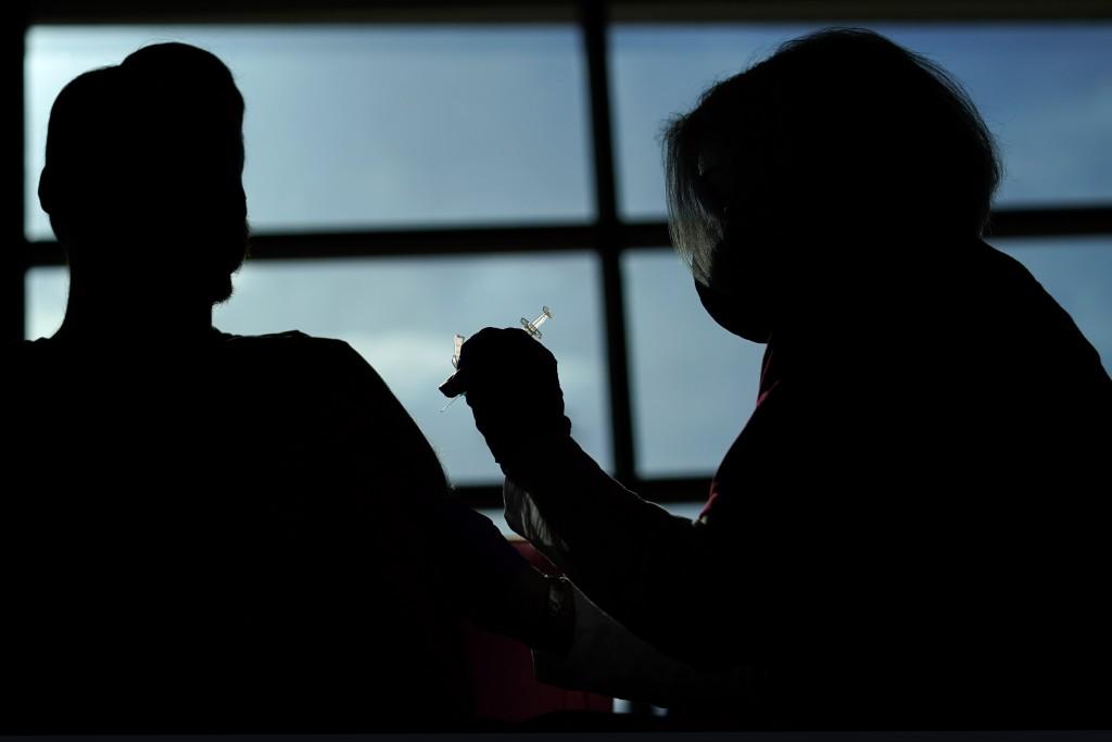 Philadelphia Flyers ice crew member Ryan DiFilipo, left, receives a Johnson & Johnson COVID-19 vaccination from nurse practitioner Erin McMenamin at t...