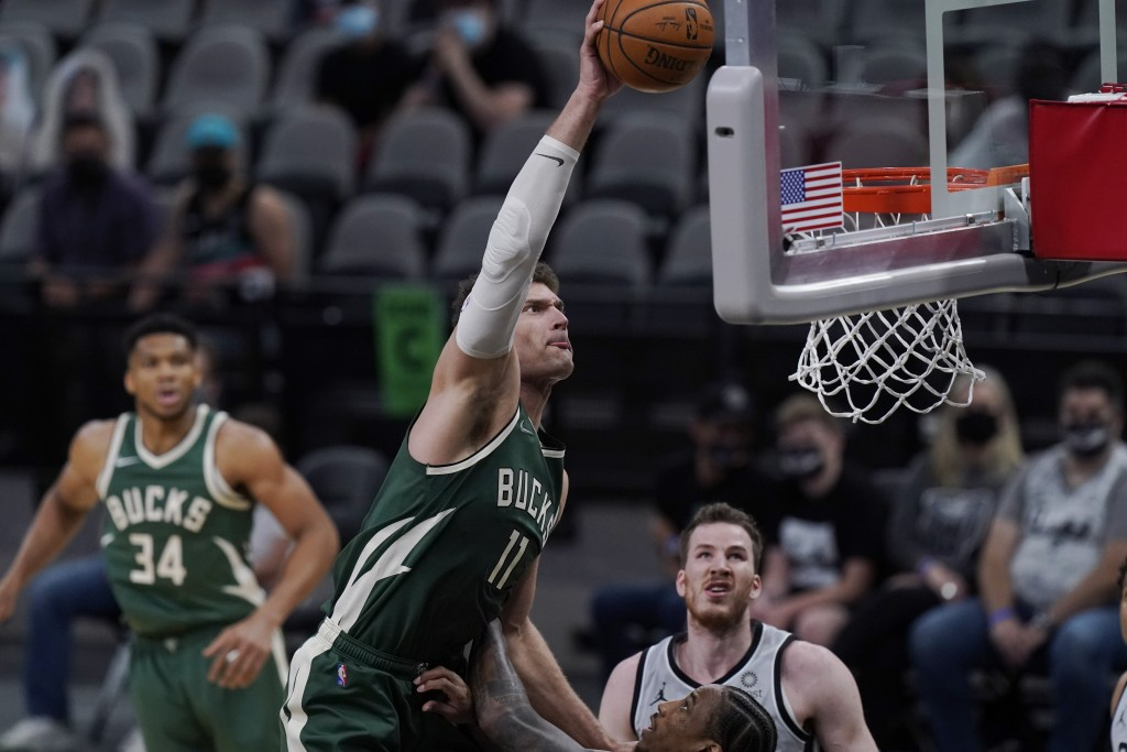 Milwaukee Bucks center Brook Lopez (11) scores over San Antonio Spurs forward DeMar DeRozan during the first half of an NBA basketball game in San Ant...