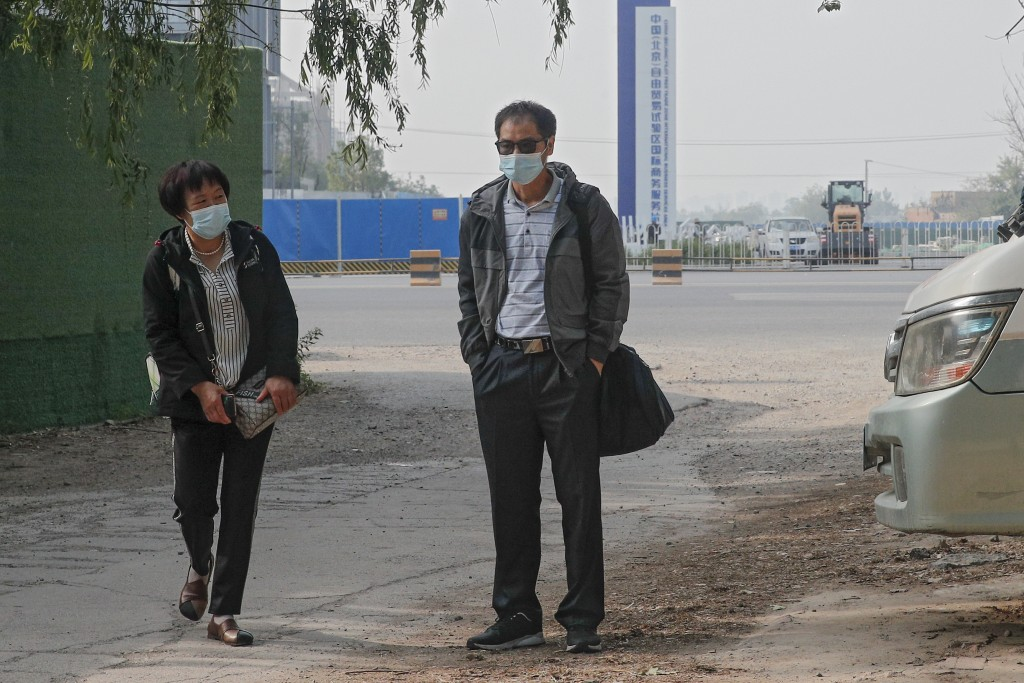 Wei Xiuwen, left, mother of Chen Mei, and Cai Jianli, center, father of Cai Wei arrive outside a courthouse to attend their children's court cases in ...