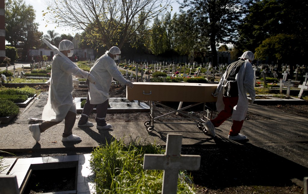 Cemetery workers push the coffin of a COVID-19 victim at a cemetery in Buenos Aires, Argentina, Saturday, May 8, 2021. Argentina has so far reported m...