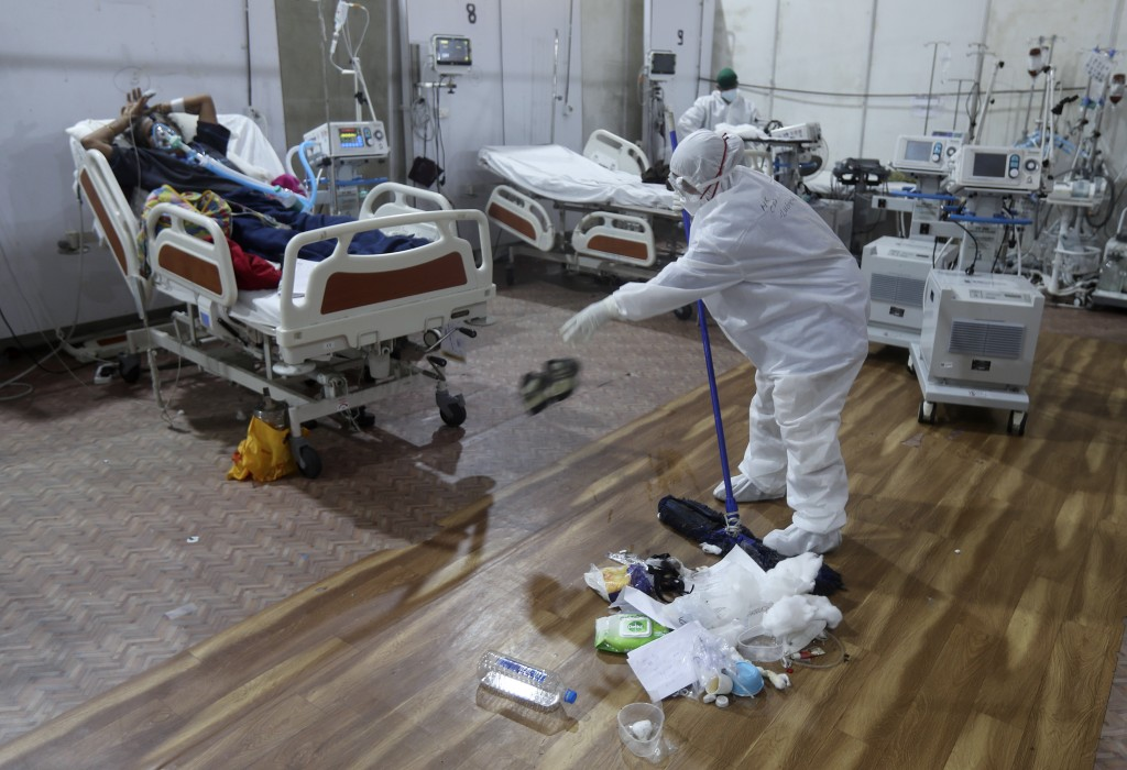 A cleaner tosses aside a pair of sandals as she does her rounds at the BKC jumbo field hospital, one of the largest COVID-19 facilities in Mumbai, Ind...