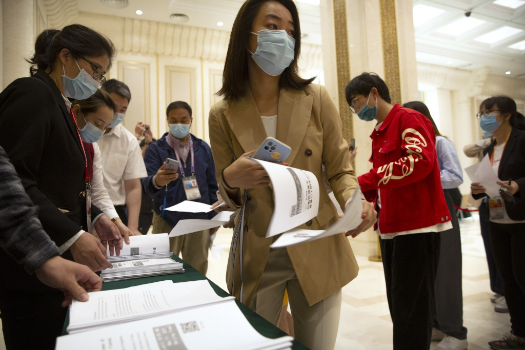 Journalists line up for copies of a news release outlining the results of China's latest population census before a press conference at the State Coun...