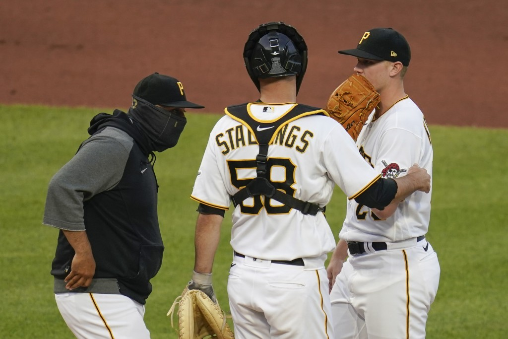 Pittsburgh Pirates pitching coach Oscar Marin, left, talks with starting pitcher Mitch Keller, right, and catcher Jacob Stallings after the Cincinnati...