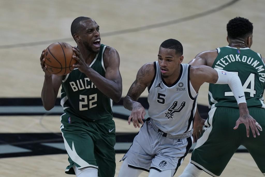 Milwaukee Bucks forward Khris Middleton (22) drives around San Antonio Spurs guard Dejounte Murray (5) during the first half of an NBA basketball game...