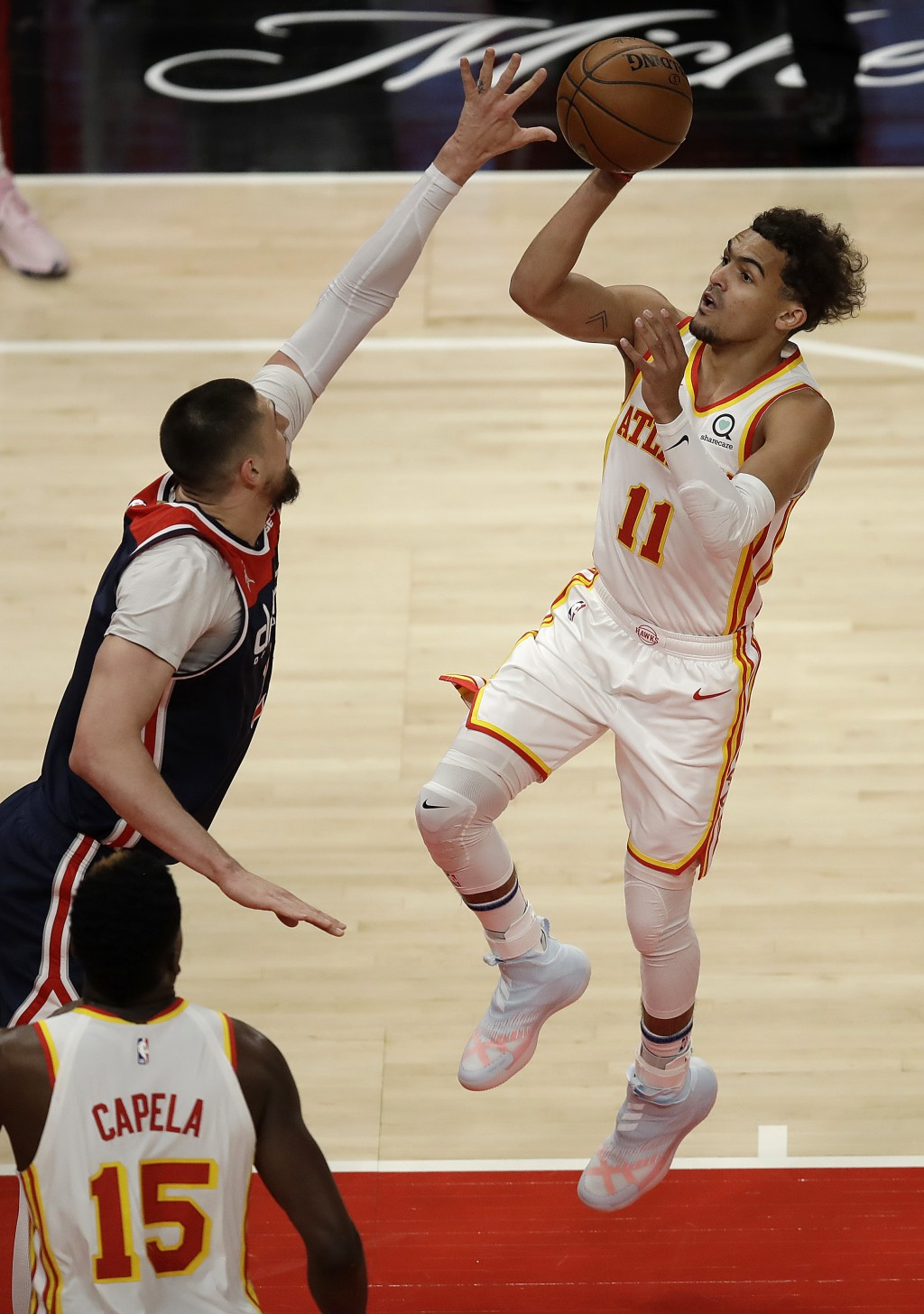 Atlanta Hawks' Trae Young, right, shoots over Washington Wizards' Alex Len during the first half of an NBA basketball game Monday, May 10, 2021, in At...