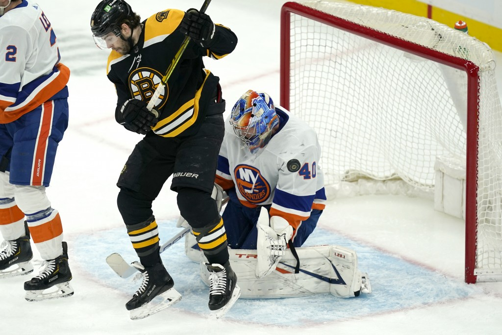 Boston Bruins left wing Jake DeBrusk (74) jumps to allow room for the puck which flies wide of New York Islanders goaltender Semyon Varlamov (40) in t...