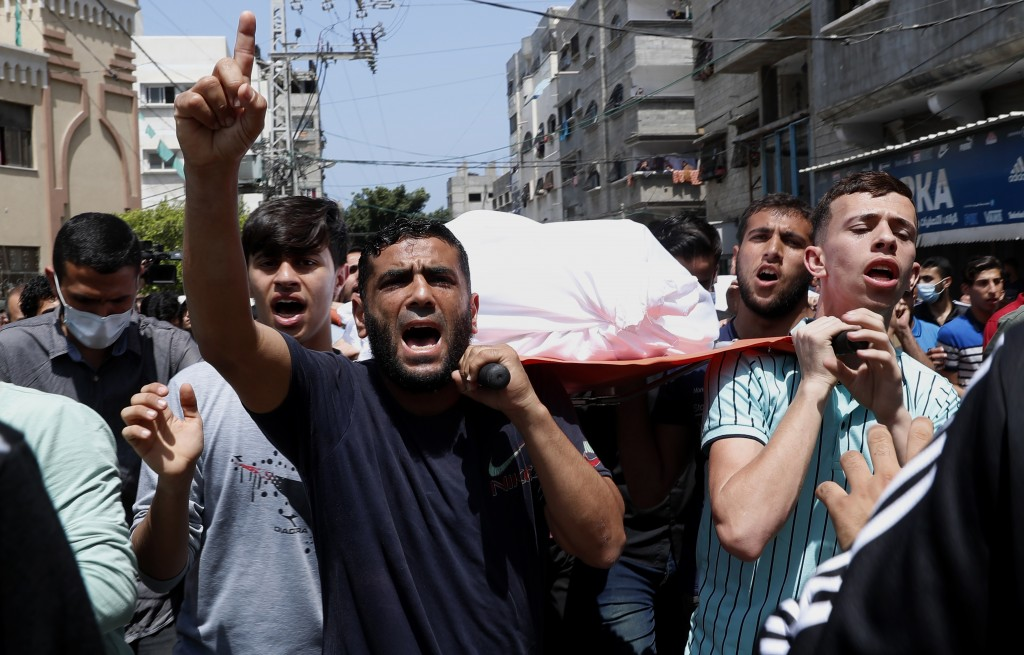 Mourners chant Islamic slogans while they carry the body of Amira Soboh, and her 19-year-old disabled son Abdelrahman, who were killed in Israeli airs...