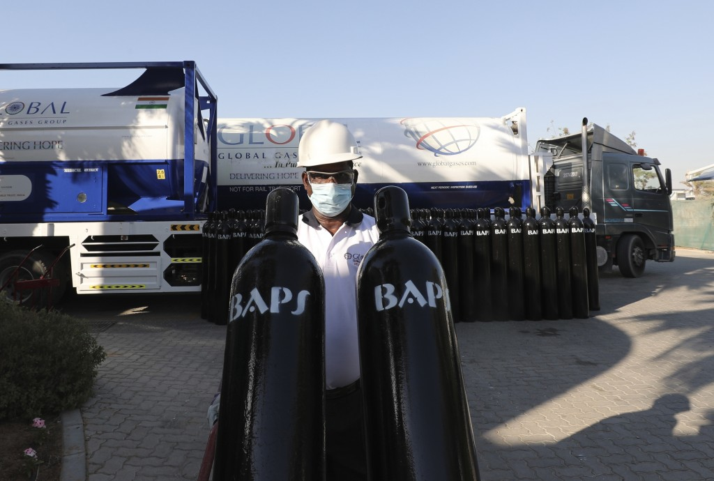 A volunteer carries containers of compressed oxygen before supplies are shipped to India, in Jebel Ali Free Zone, Dubai, United Arab Emirates, Monday,...