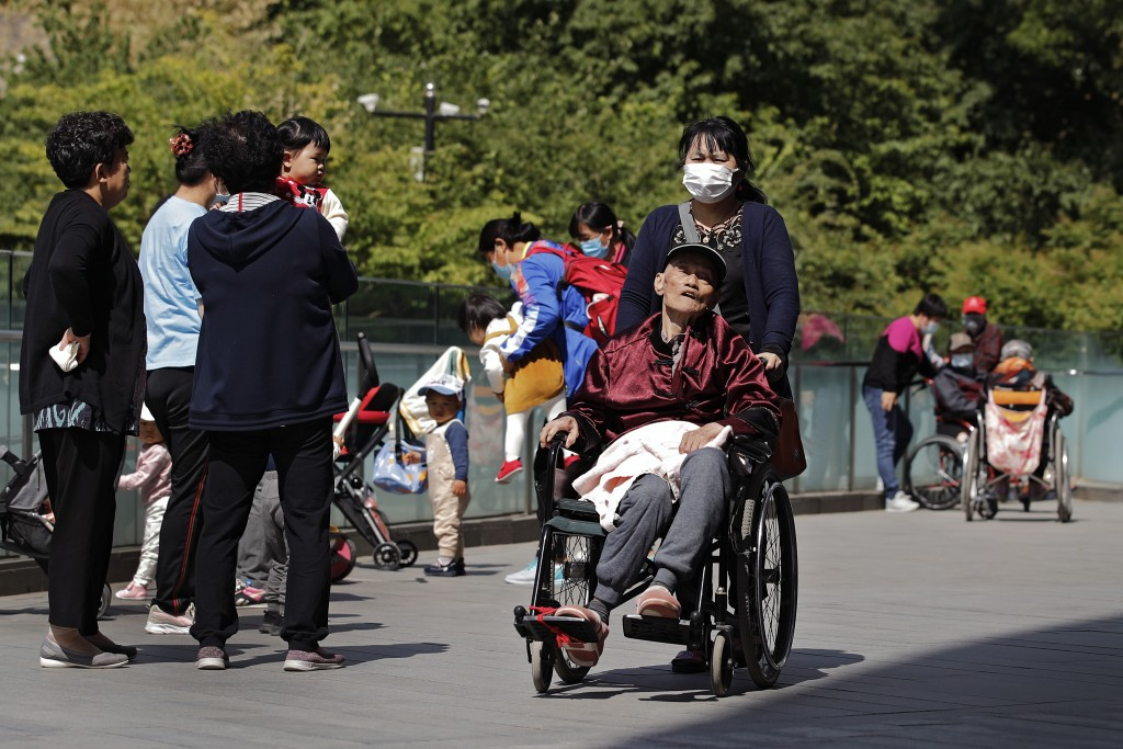 A woman wearing a face mask pushes an elderly man on a wheelchair passes by residents play with their children near a commercial office building in Be...