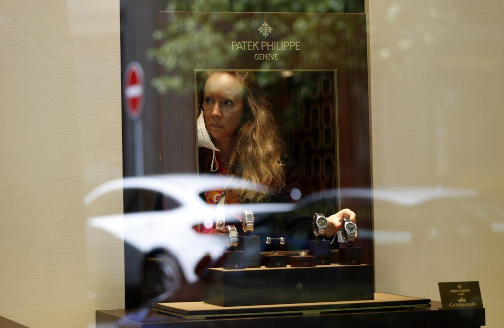 A woman adjusts watches in a shop in Prague, Czech Republic, Monday, May 10, 2021. The Czech Republic is massively relaxing its coronavirus restrictio...