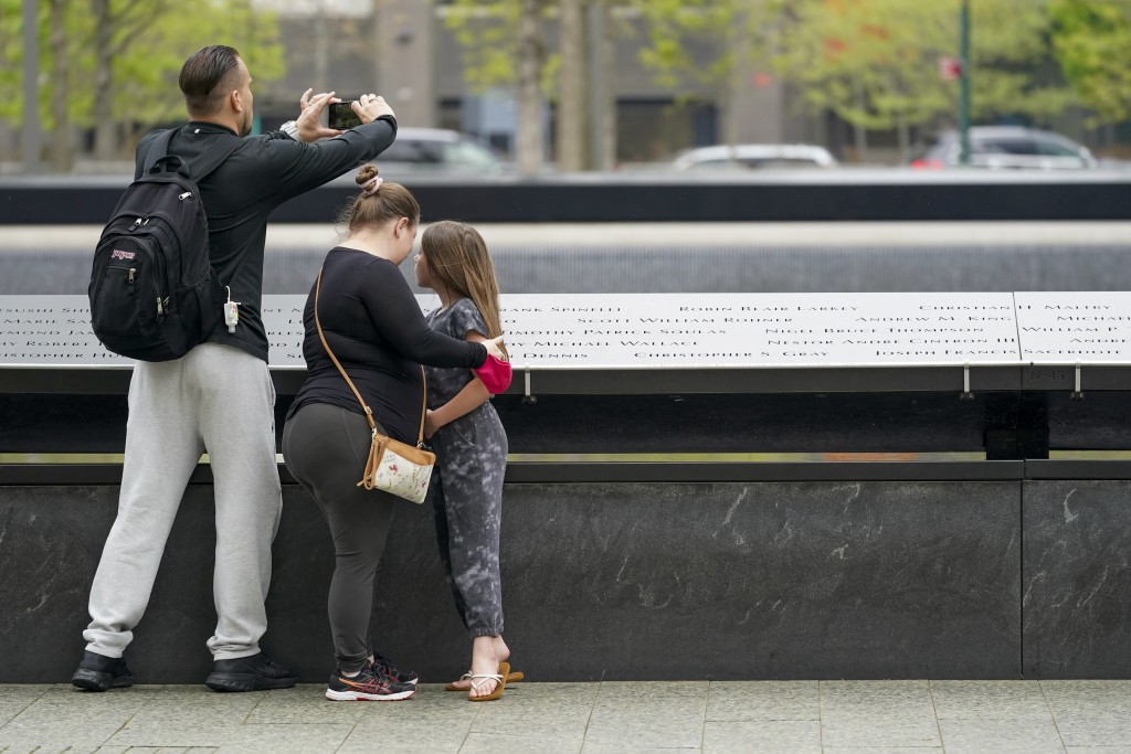 Visitors to the 9/11 Memorial and Museum take in the view of the North Pool, Thursday, April 29, 2021, in New York. In recent weeks, tourism indicator...