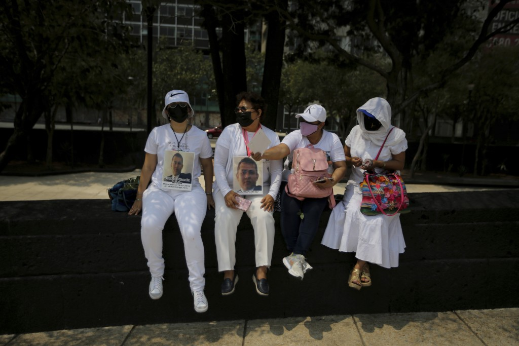 The relatives of disappeared people sit on the sidelines of a march in remembrance of those who have disappeared, on Mother's Day in Mexico City, Mond...